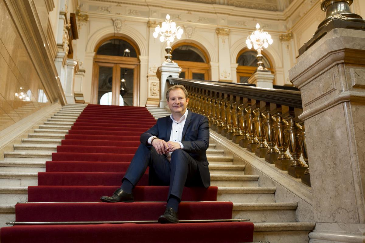 Jens Kerstan sitzt auf Stufen im Hamburger Rathaus
