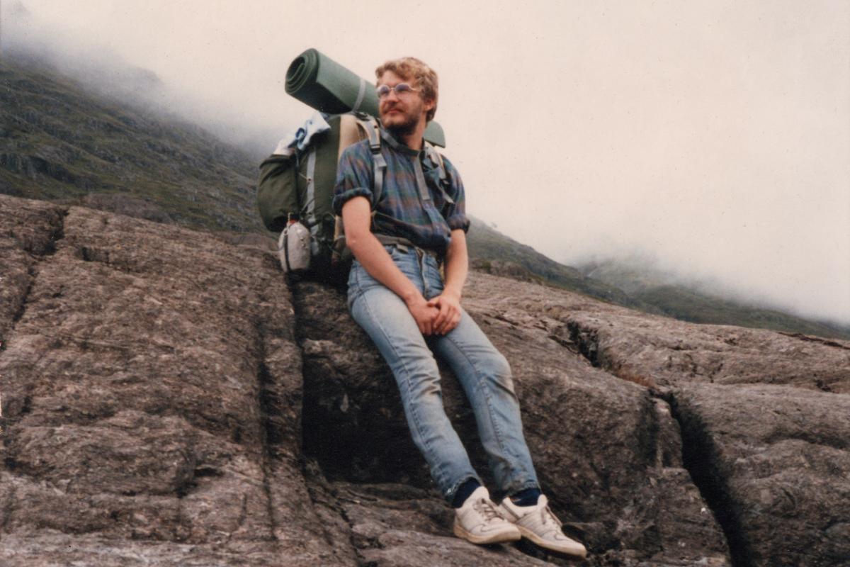 Jens Kerstan lehnt mit Reiserucksack auf dem Rücken an einem Berg