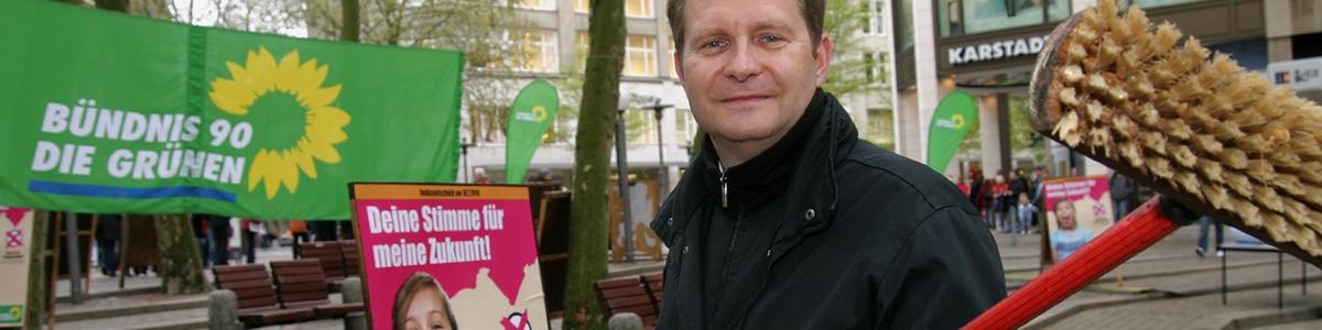Jens Kerstan mit Schrubber in der Hand, im Hintergrund Wahlplakate